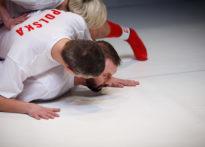 Aktorzy lezący na sobie na białym podłoży w biało czerwonych strojach