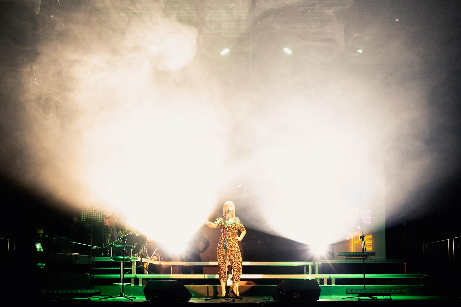 Aktorka stojąca na scenie w świetle reflektorów