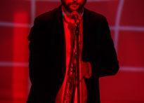 Aktor stojący przy mikrofonie z trąbką w ręce na czerwonym tle