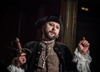 Aktor stojący na ciemno złotym tle, ubrany w gustowny strój, z piracką czapką nagłowiei mocno wymalowanymi oczami, trzymający w ręku sztylet. Na zdjęciu Jakub Papuga
