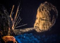 Dziecięca buzia narysowana na czarnym tle, wypuszczająca z ust podmuch powietrza.
