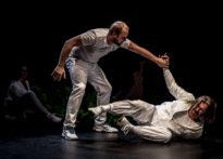 Leżący na scenie aktor i mężczyzna trzymający do za rękę, W tle postać kobiety