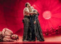 Leżąca na scenie kobieta, za nią tuląca się para. w tle głowy chóru wychodząca ze scenografii