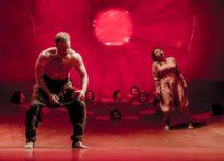 Kobieta i mężczyzna w różnych pozach stojący na scenie, za ich plecami głowy chóru wychodzące ze scenografii