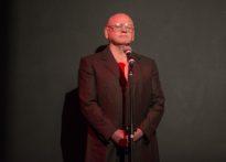 Łysy mężczyzna w okularach stojący przy mikrofonie na czarnym tle