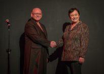 Kobieta i mężczyzna na tle czarne ściany ściskający sobie dłonie