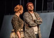 Aktor i aktorka stojący na scenie i rozmawiający ze sobą