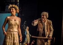 Na pierwszym planie aktora w sukni ślubnej i wianku na głowie na drugim planie aktor z siekierą w dłoni i figura Matki Bożej