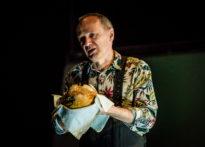 Aktor ubrany w kwiecistą koszule trzymający w rękach chleb.