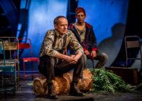 Aktor siedzący na pniu palmy, za nik drugi aktor siedzący na krześle.
