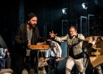 Aktor w czapce przy instrumencie , koło niego drugi aktor wyciągający do niego ręce. W tle pozostali aktorzy