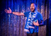 Aktor na tle brokatowej kotary ubrany w barwy poznańskiego klubu Lech Poznań z szalikiem na szyi oraz piłką w ręce.Na zdjęciu Jakub Papuga