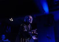 Aktor ubrany w porannik, z tyłu członek orkiestry. Na zdjęciu Wiesław Zanowicz
