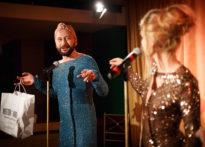 Aktor ubrany w damką sukienkę trzymający torbę papierową oraz aktorka ubrana w sukienkę z cekinami. Na zdjęciu Jakub Papuga oraz Agnieszka Findysz