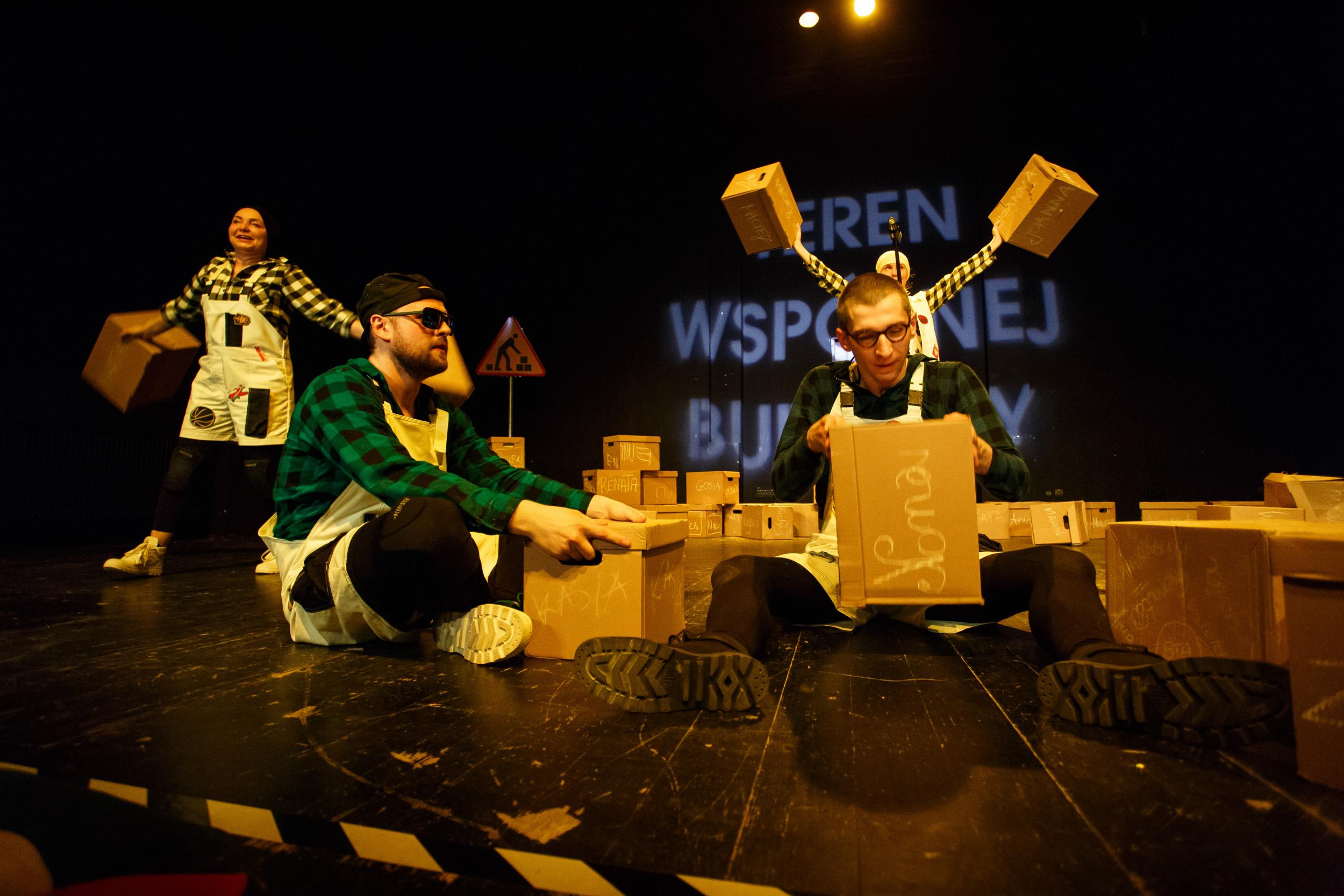 Aktorzy w rożnych pozach na scenie z kartonami w rękach