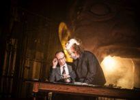 Aktor siedzący przy stole w towarzystwie drugiego aktora stojącego nad nim, który na głowie ma założoną maskę klauna. W tle wielka buzia z otwartą jamą ustną