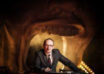 Aktor siedzący przy stole, ubrany w garnitur na tle wielkiej jamy ustnej