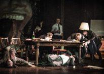 Kobieta i mężczyzna w pozycji leżącej, jedno na ziemi drugie na krześle, dwóch mężczyzn leżących na stole oraz trzech mężczyzn stojących za stołem
