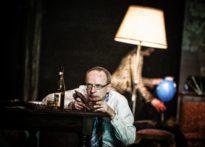 Na pierwszym planie aktor kucający przy stole jedzący sztuczną wątrobę, na drugim planie stojąca aktora z niebieskim balonem w ręce