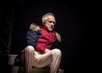 Aktor siedzący na schodach w czerwono granatowej marynarce.
