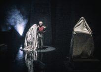 Aktor stojący przy pulpicie do nut, koło niego jak i przed nim stoją postacie w prześcieradłach