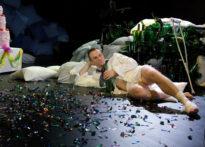 Aktor ubrany w koszule, leżący na ziemi z butelką w ręce. W tle scenografia wykonana ze szklanych butelek