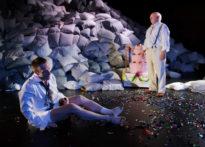 Aktor ubrany w koszule siedzący na ziemi bez spodni , koło niego mężczyzna stojący koło tortu.W tle scenografia z poduszek.