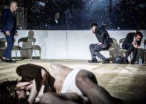 Na pierwszym planie leżąca kobieta w białej bieliźnie, dalej aktor uchwycony w ruchu oraz dwóch aktorów udających wymioty na tle luster.Na zdjęciu Kaya Kołodziejczak, Jerzy Walczak, Piotr Dąbrowski oraz Konrad Cichoń