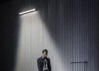 Akor z rękoma w kieszeni stojący na scenie w świetle jarzeniówki