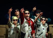 Piątka aktorów w czapkach i okularach przeciwsłonecznych wśród kartonów wskazująca coś palcem