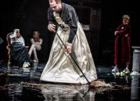 Aktor ubrany w spódnicę sprzątający scenę, w tle trzy kobiety w rożnych pozach