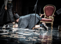 Aktor klęczący na scenie przy stopie kobiety