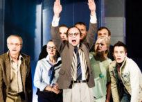 Mężczyzna z rękoma uniesionymi do góry, zanim pozostali aktorzy