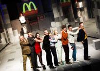 Zdjęcie zbiorowe aktorów stojących na scenie- w tle logo Macdonalda