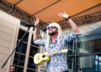 Aktor z peruką na głowie i ukulele przewieszonym przez szyję stojący na scenie z rękoma w górze
