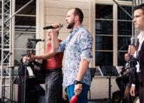 Aktorzy stojący na scenie , gdzie jeden z nich śpiewa do mikrofonu