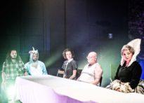 Pięć postaci siedzących przy stole- mężczyzna w kraciastej koszuli, mężczyzna w stroju jednorożca, kobieta w sukience, mężczyzna w białym podkoszulku oraz kobieta w czarnej sukni z dużym stojącym ponad głowę kołnierzem.