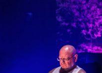 Mężczyzna w białym podkoszulku siedzący za stołem, w tle wyświetlona fototapeta