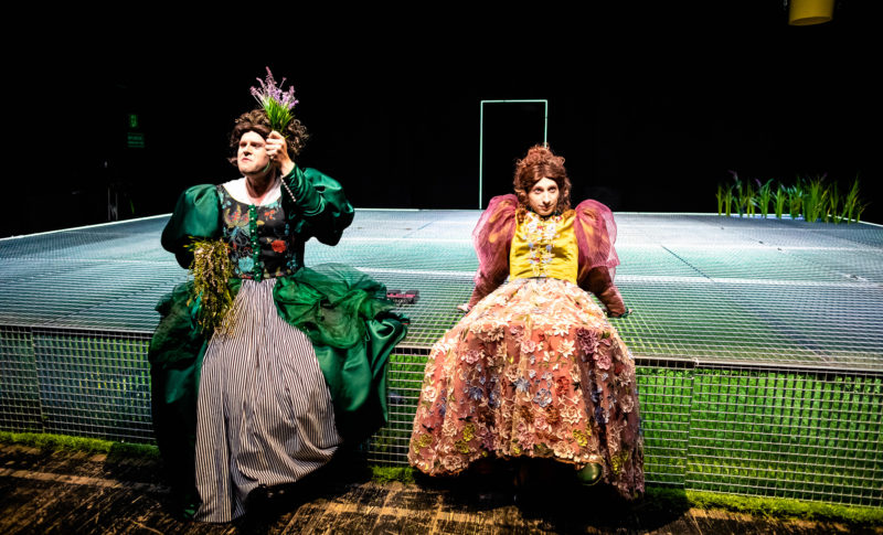 Dwóch mężczyzn ubranych w peruki i damskie suknie siedzących na metalowej kracie. Jeden z nich trzyma w rękach sztuczne kwiaty.