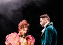 Dwóch mężczyzn stojących w świetle i otoczonych kłębem dymu. Jeden ubrany w damska suknię, drugi w strój epokowy