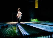 Mężczyzna stojący wewnątrz metalowej konstrukcji uchwycony w trakcie ubierania. Za jego plecami sztuczna roślinność umieszczona w metalowej kracie oraz żółty spad widzący pod sufitem.