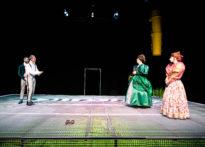 Czterech mężczyzn stojacych na metalowej kracie, dwóch ubranych w peruki i damskie suknie i dwóch w epokowych strojach.
