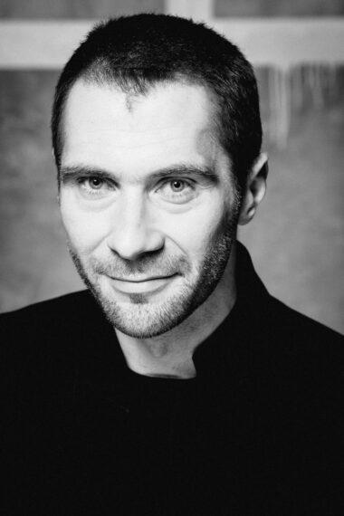Czarno-biała fotografia. Uśmiechnięty mężczyzna z zarostem wpatruje się w obiektyw. Ubrany jest na czarno. Na zdjęciu: Piotr B. Dąbrowski.