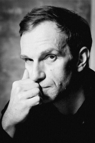 Czarno-biała fotografia. Mężczyzna wpatruje się w obiektyw, trzyma jedną dłoń zwiniętą w pięść przy twarzy. Na zdjęciu: Michał Kaleta.