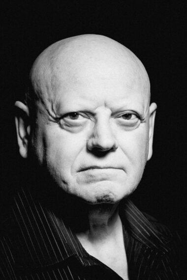 Czarno-biała fotografia. Łysy mężczyzna patrzy się w obiektyw. Wokół niego czarne tło. Na zdjęciu: Wojciech Kalwat.