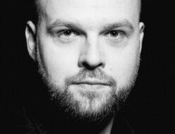 Mężczyzna na czarno-białej fotografii. Na zdjęciu Mariusz Adamski.