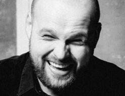 Roześmiany mężczyzna na czarno-białej fotografii. Na zdjęciu Mariusz Adamski.