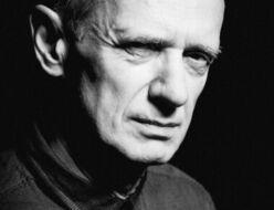 Czarno-biała fotografia. Mężczyzna obrócony profilem wpatruje się w obiektyw. Ma na sobie koszulę. Na zdjęciu: Andrzej Szubski.