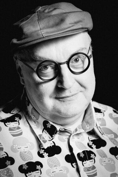 Czarno-biała fotografia. Męzczyzna w berecie w okrągłych okularach z grubymi oprawkami wpatruje się w obiektyw. Ma na sobie koszulę w motyw gejsz. Na zdjęciu: dyrektor Maciej Nowak.