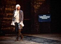 Aktor stojący na scenie w peruce i epokowym stroju. Za jego plecami ekran telewizora na którym wyświetlany jest tekst
